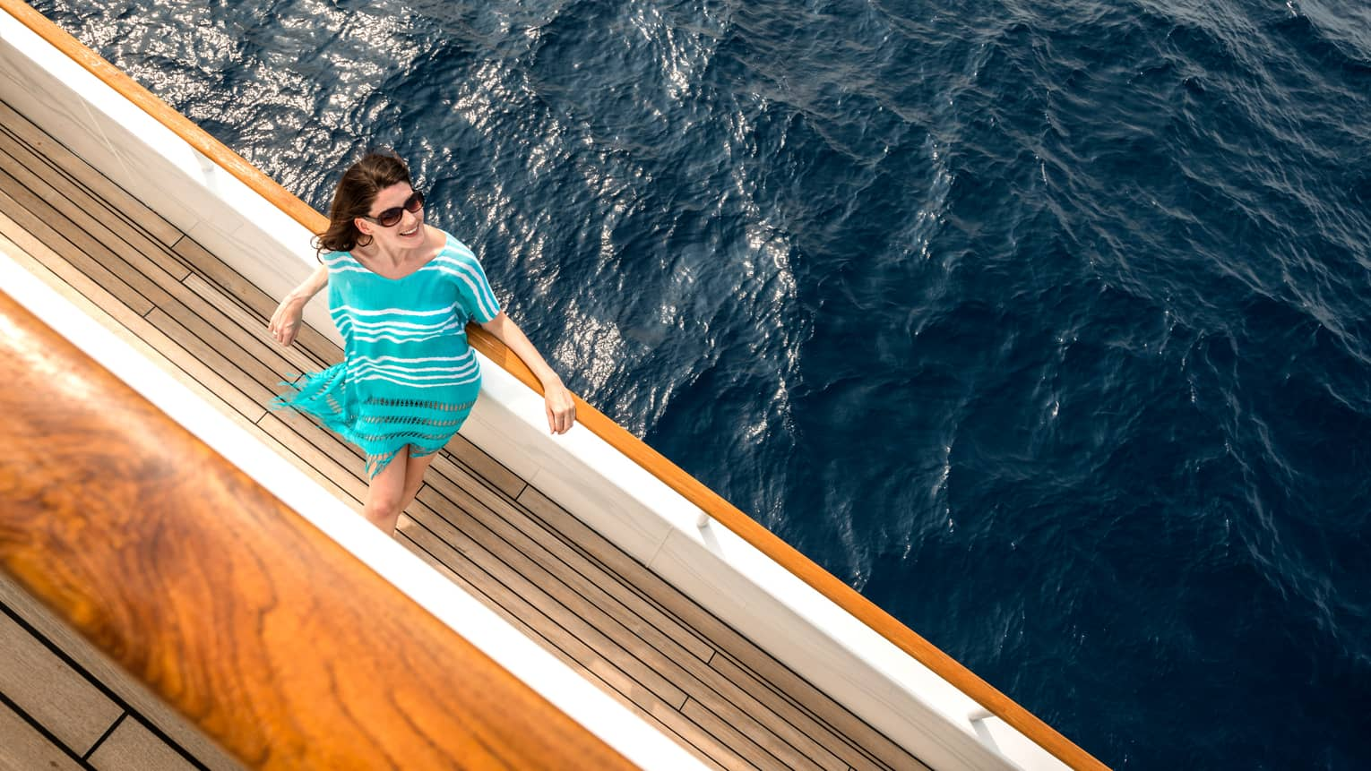 Woman wearing striped teal dress, sunglasses looks up from yacht railing