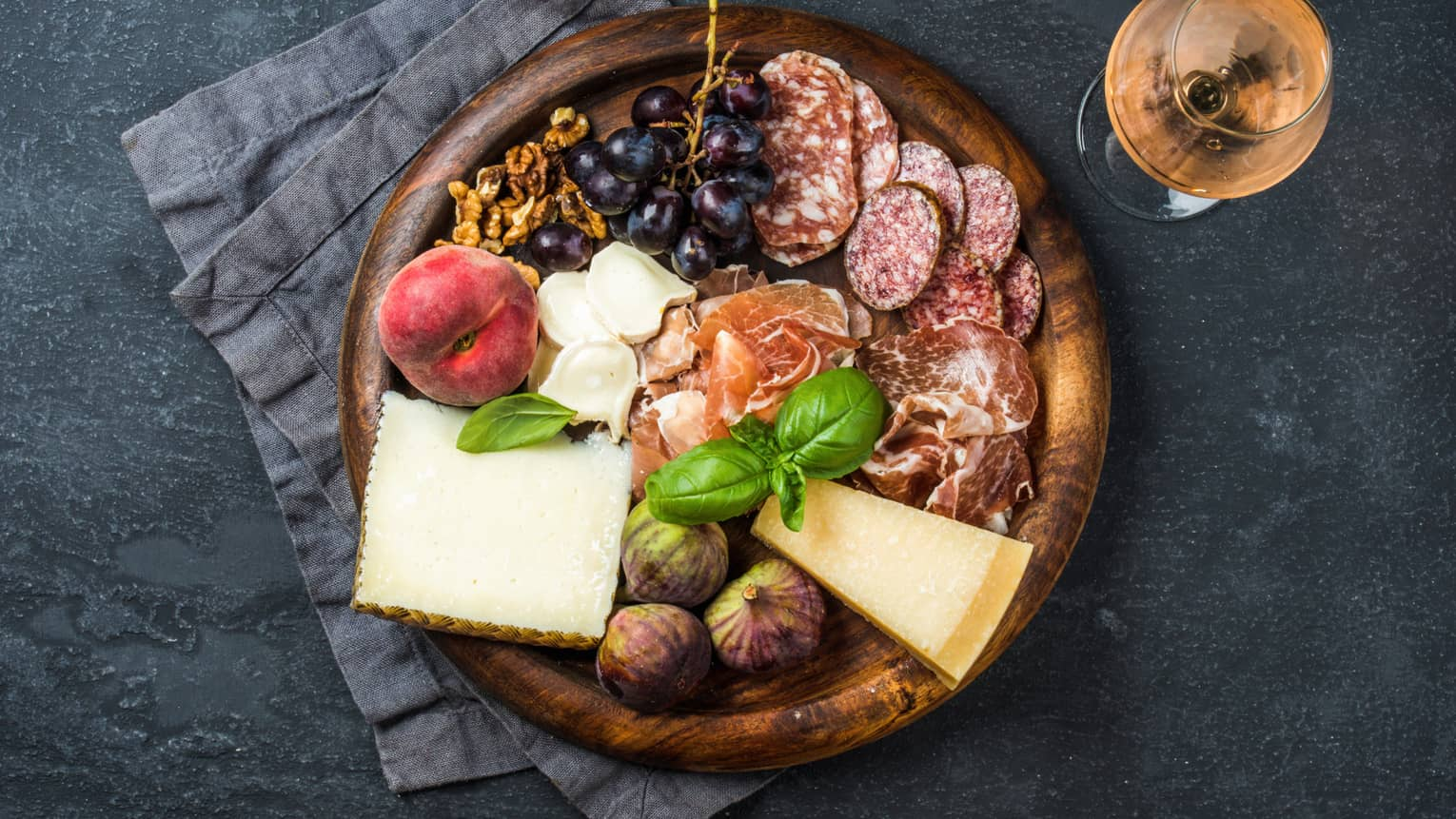 Round wood tray with fresh cheese, cured meats, figs, grapes, nectarine