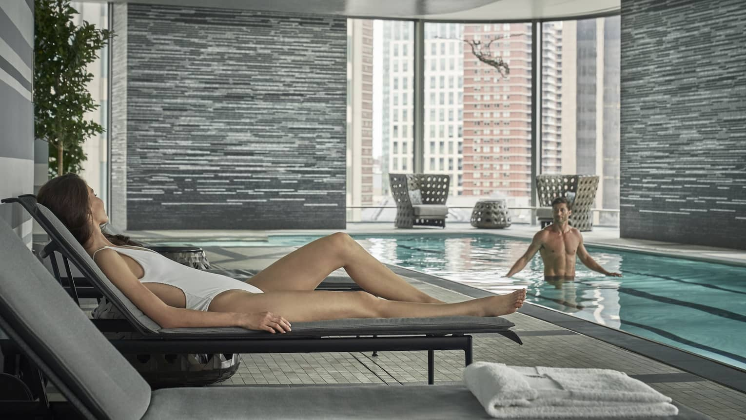 A woman in a white bathing suit and lounger looks on at her significant other at the lap pool in the Spa.