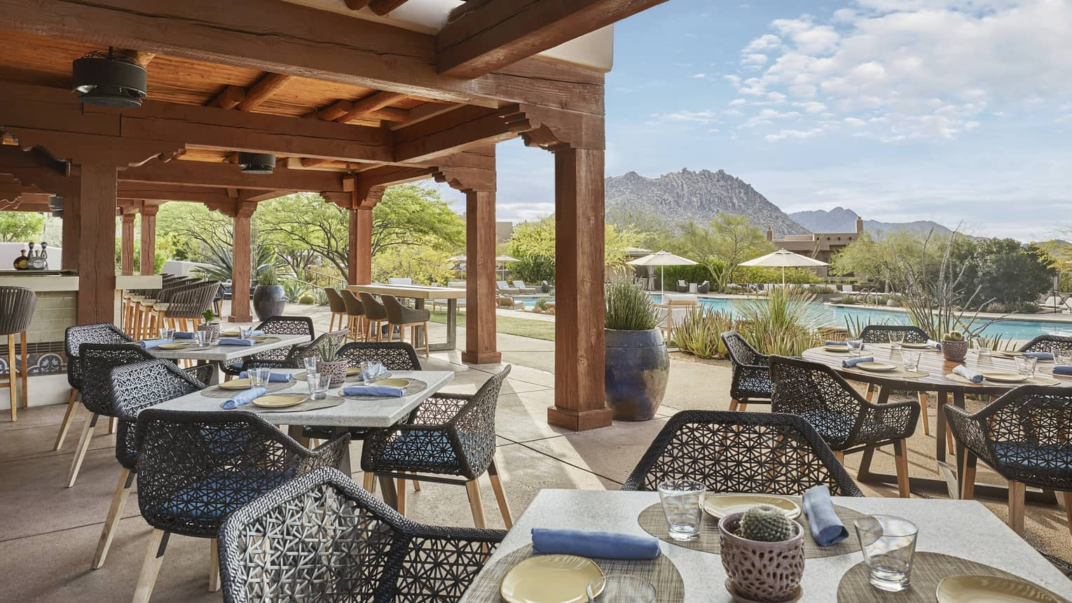 Outdoor restaurant patio with square tables, each with four dark blue wicker chairs, wooden pergola