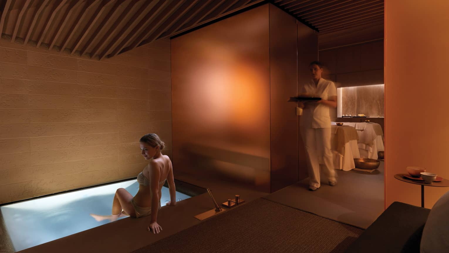 Woman in bikini lowers herself into small illuminated spa tub, staff holds tray in background