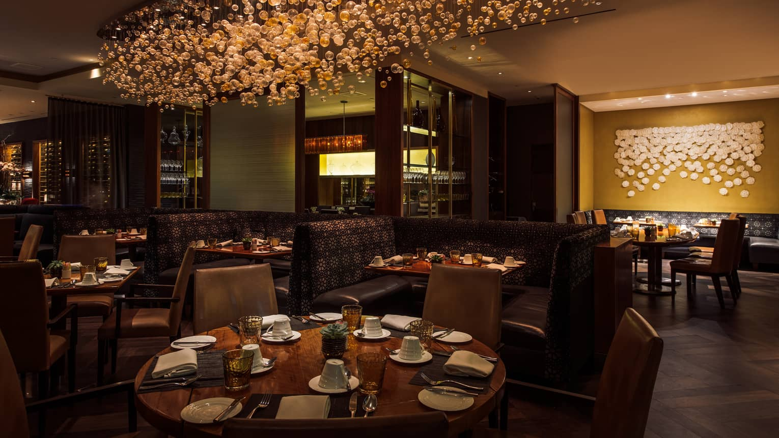Culina Restaurant round dining tables, booths under modern glass bulb chandelier