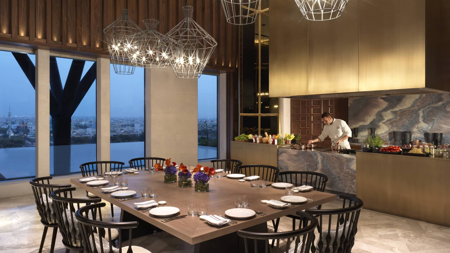 Large 10-person dining table under modern geometric wire lights, beside window and chef at marble bar