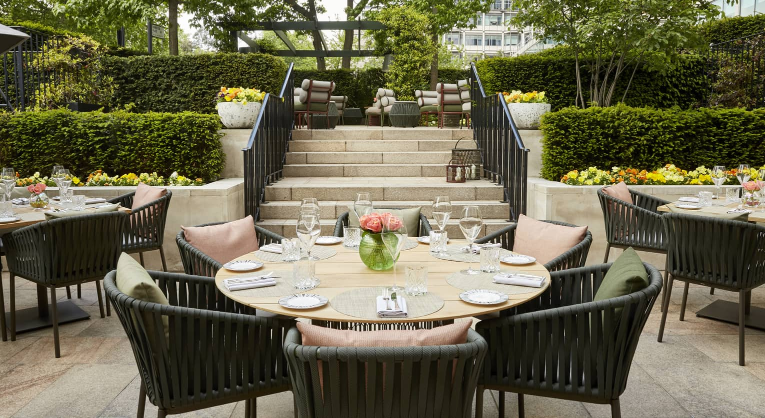 Round tables outside are decorated with place-settings and glasses for a meal