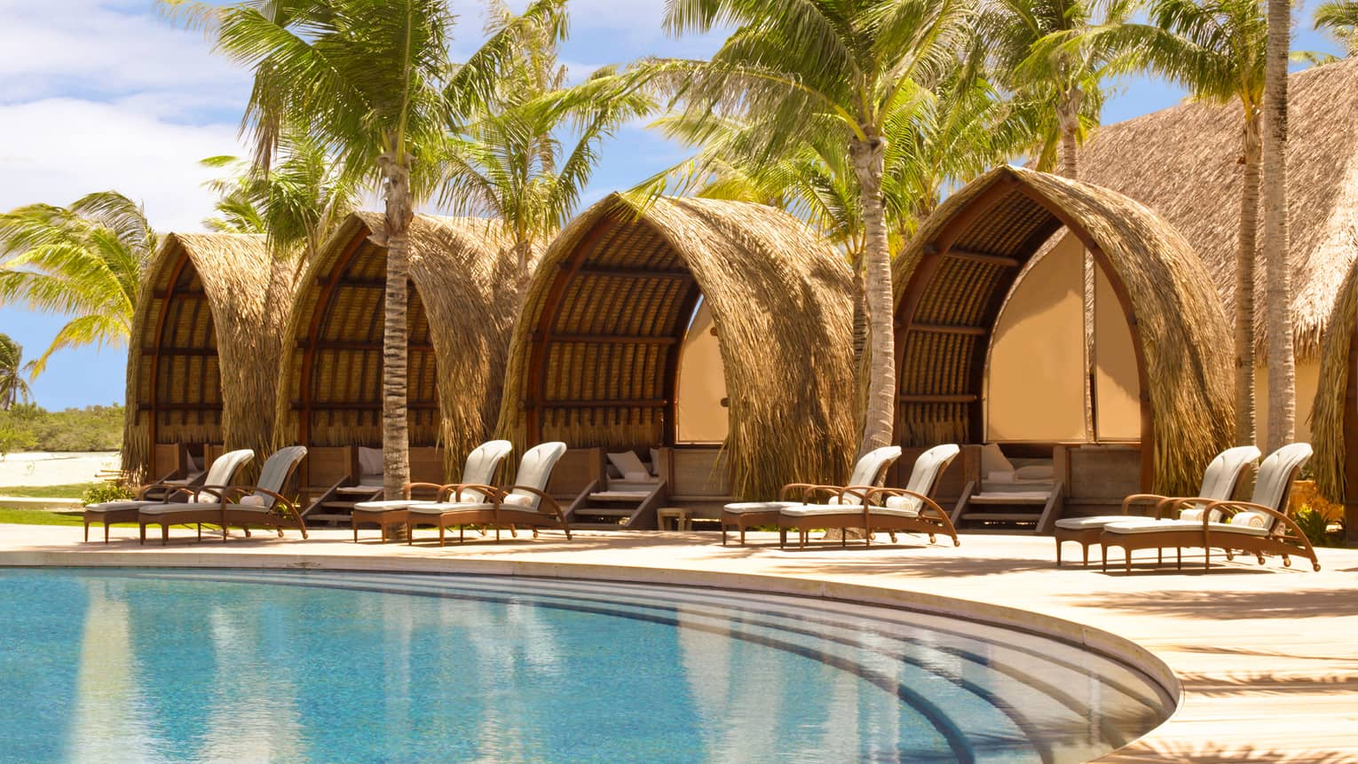 Four poolside pavilions with thatched roofs behind white lounge chairs, steps leading into swimming pool