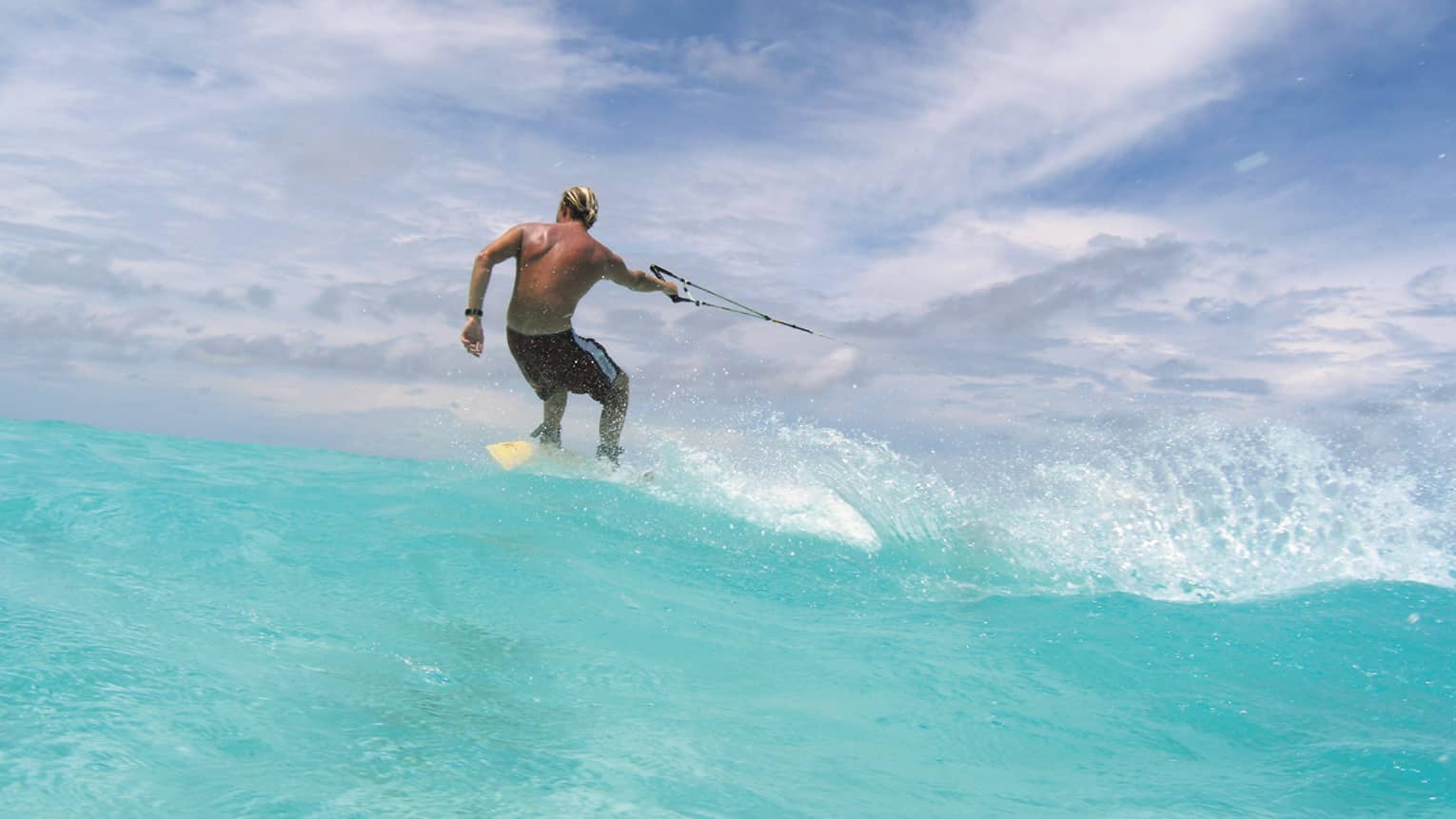 Man holds handle, wakeboards on turquoise wave in ocean