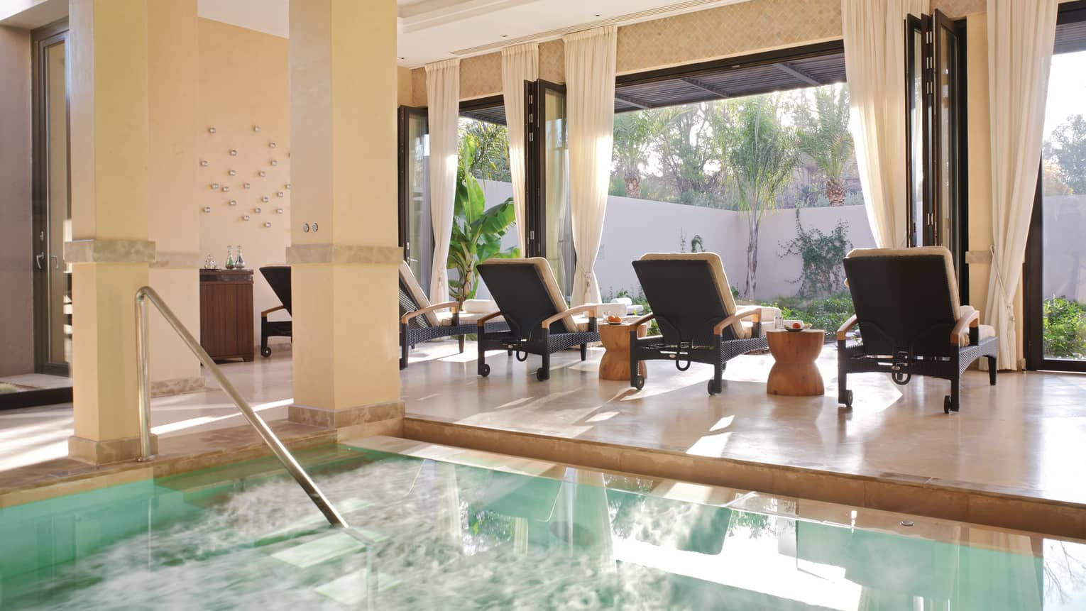 Three lounge chairs at sunny window by steps to Spa plunge pool