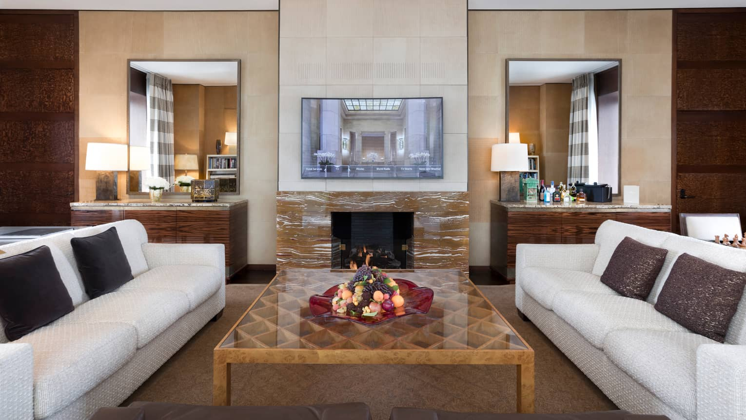 Presidential Suite white sofas around large table, wood-grain marble fireplace, TV on mantle