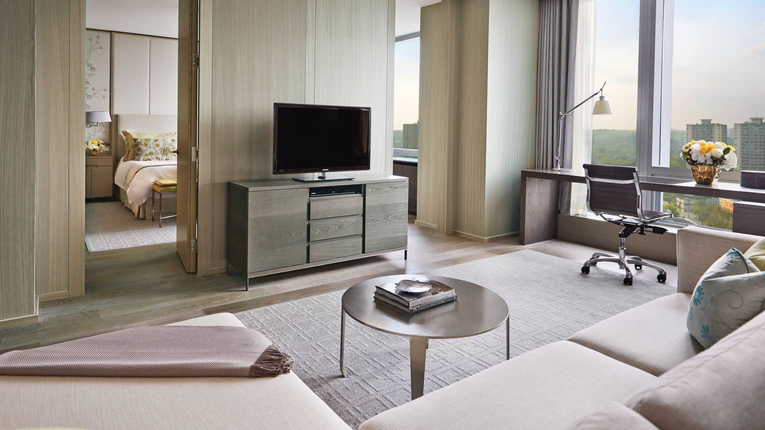 Bright, modern hotel suite, TV against birch wood wall to bedroom, desk by floor-to-ceiling window