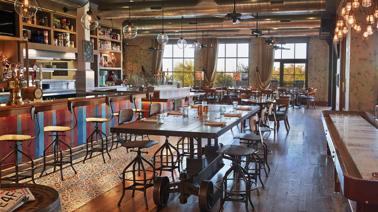 Proof bar during day, long rustic wood dining table, red-and-blue wood bar with stools, large glass bulb lights