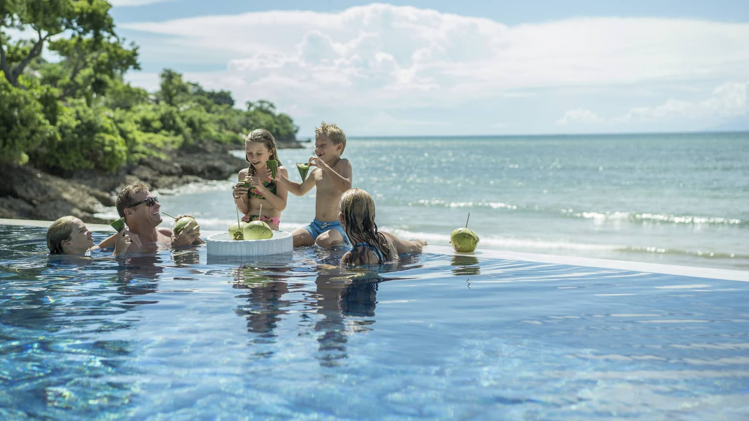 A family enjoying fresh coconuts outside in the Sundara pool