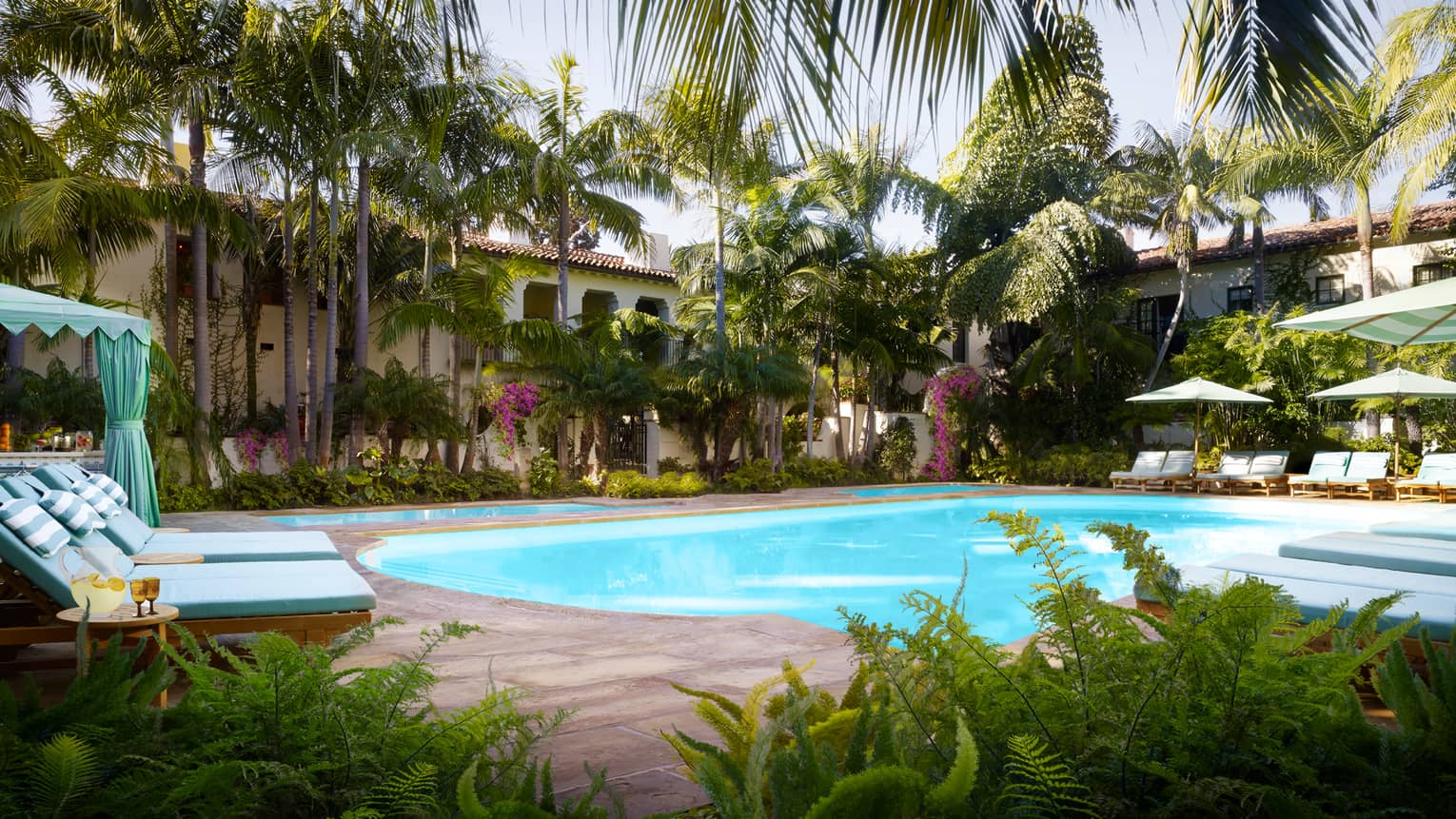 Tropical trees, plants, lounge chairs and cabanas around Jungle Pool