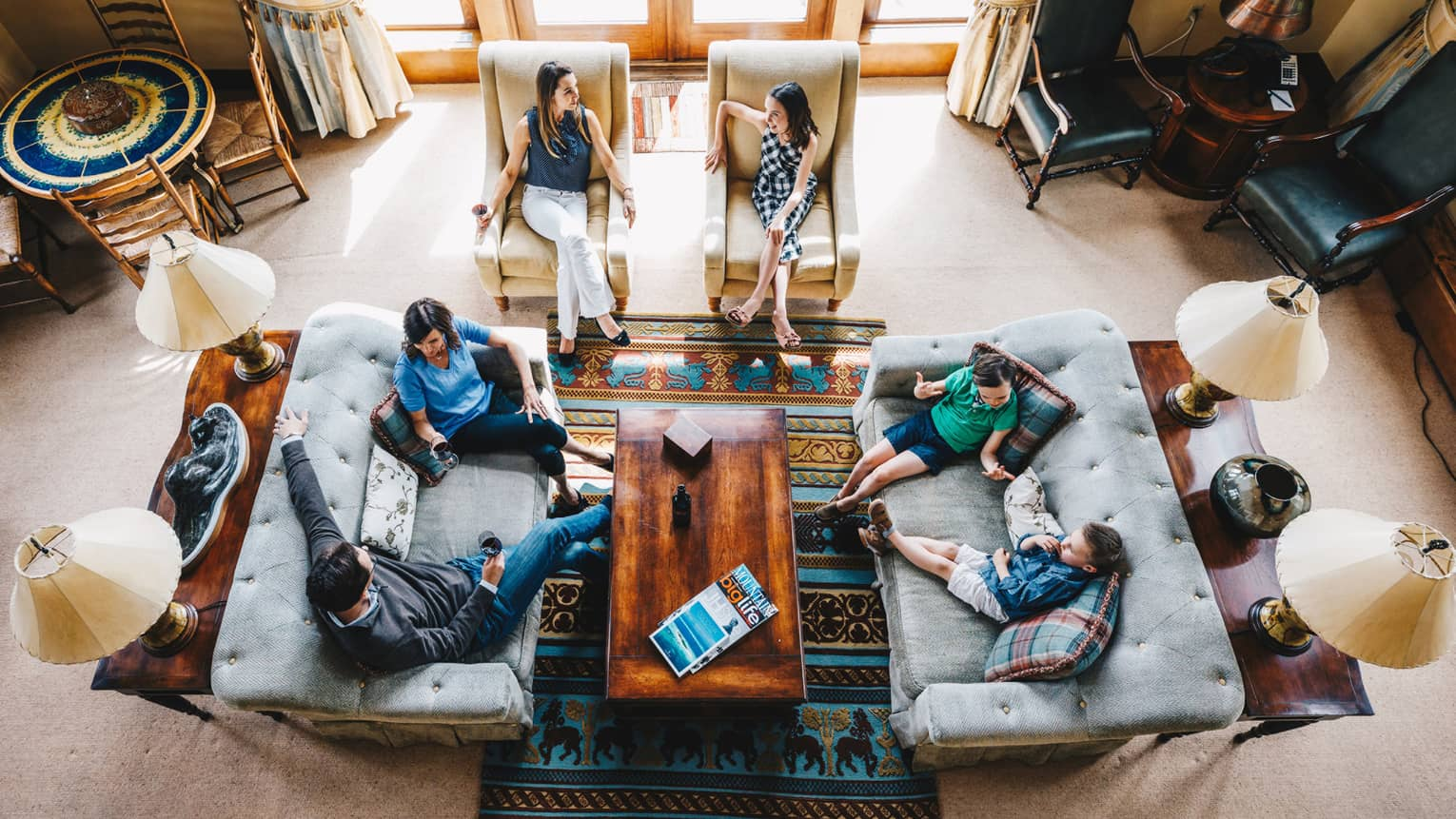 Aerial view of guests talking and relaxing in the living room of a residence