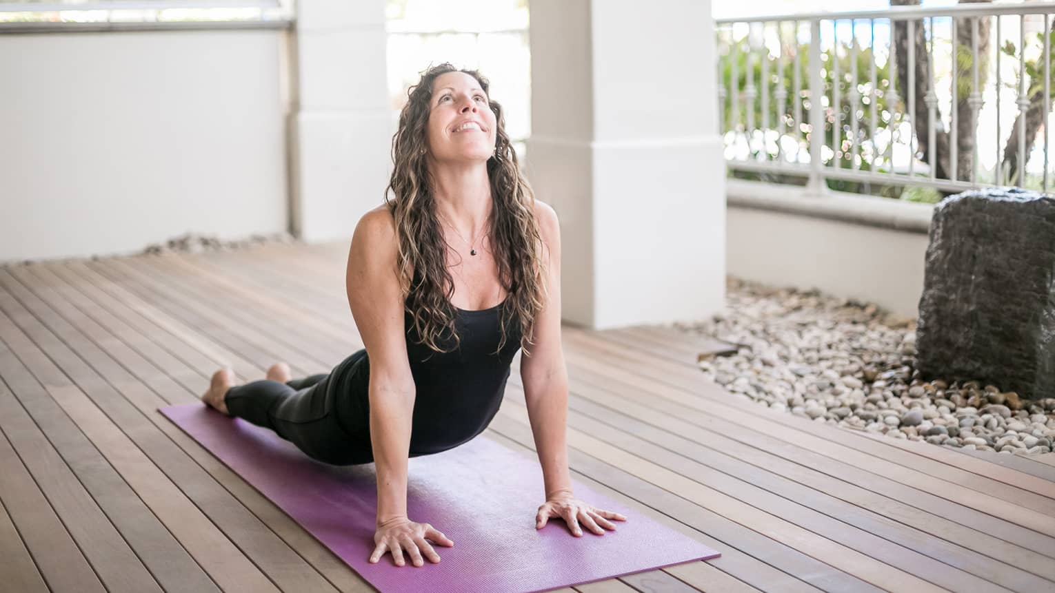 Woman smiles, looks up as she does yoga stretch on all fours on purple mat
