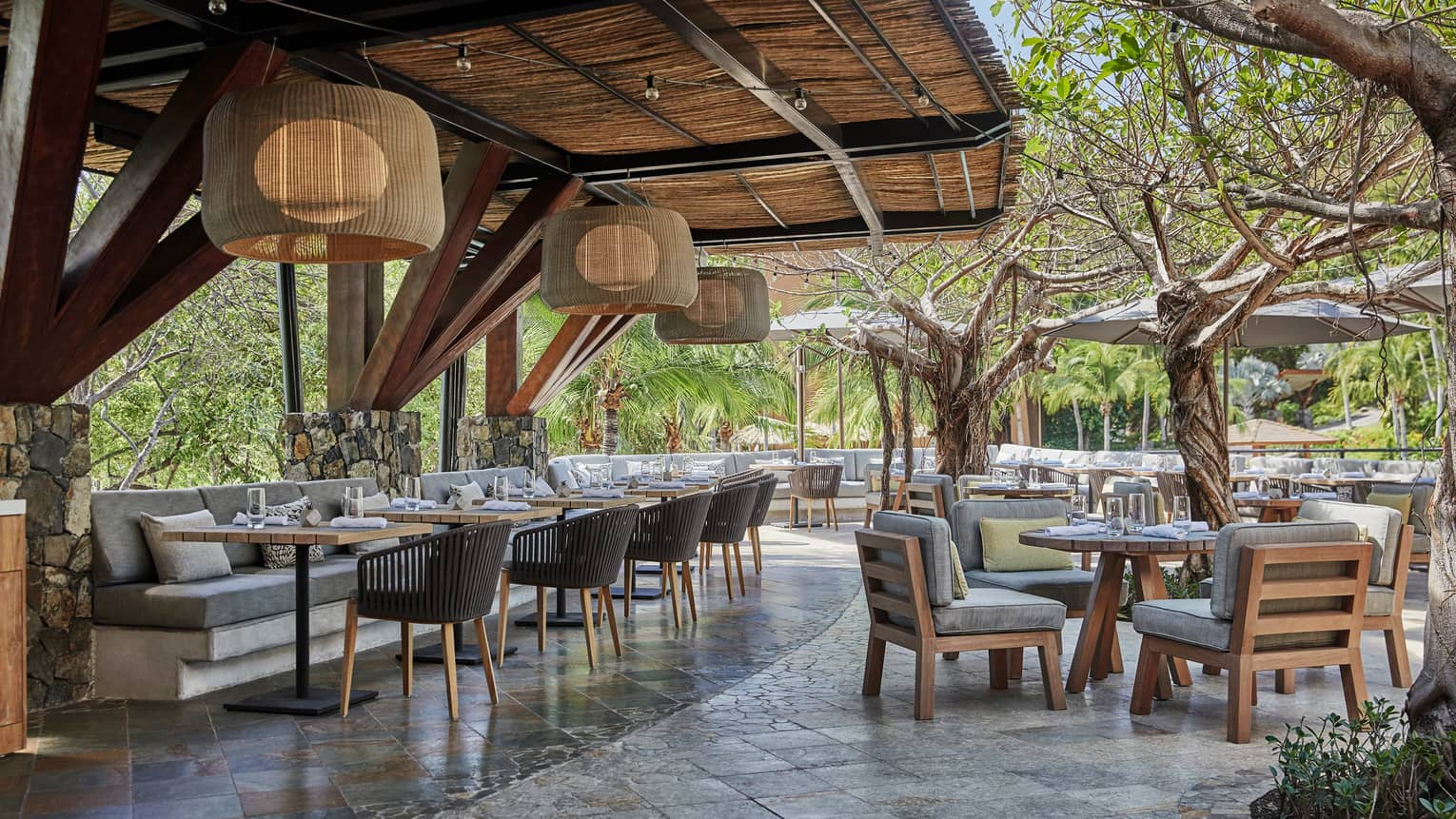 Bahia restaurant patio dining tables and chairs with thick grey cushions, large bamboo round lights hang from awning