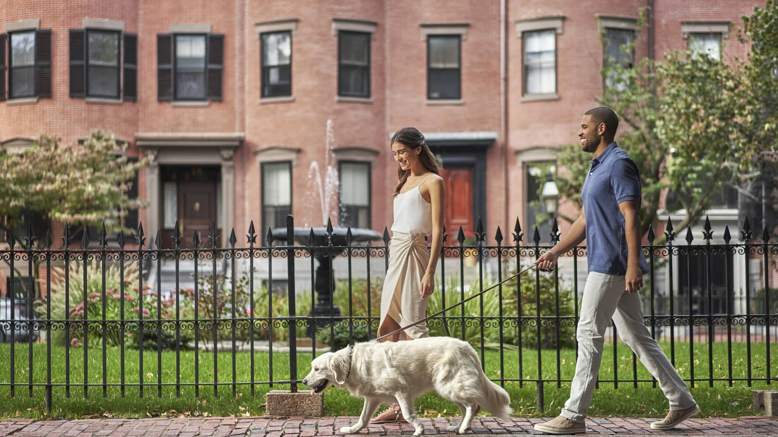 Man and woman walk their Golden Retriever in front of a Boston brownstone