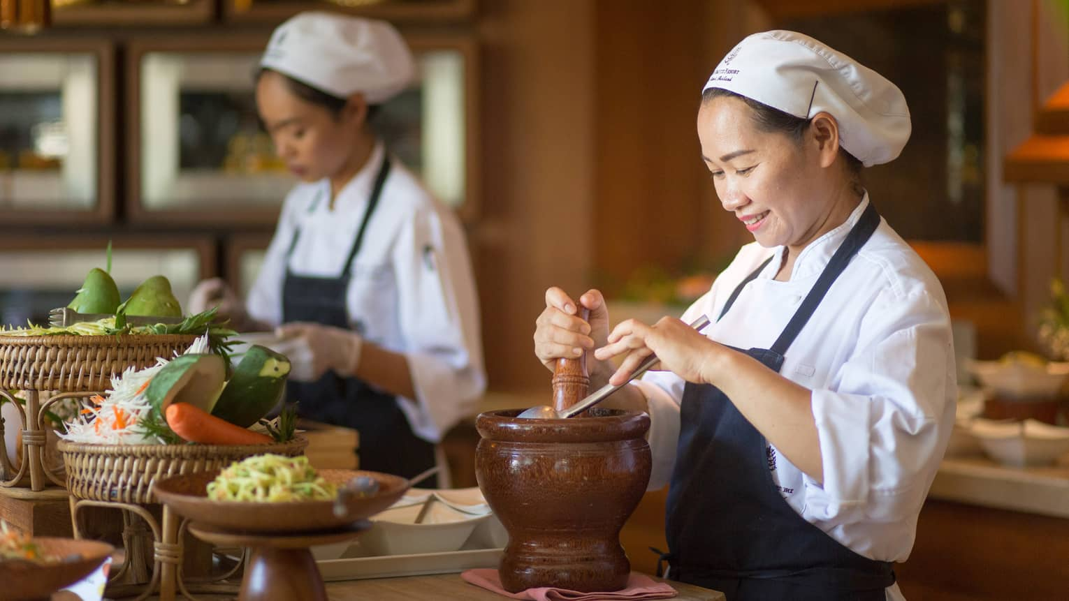 Two chefs in uniform prepare authentic Thai cuisine dishes at counter with fresh vegetables