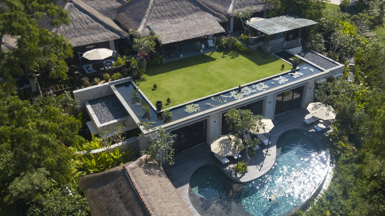 An overhead view of an Imperial Villa, with a guest enjoying the sunlight at the private pool