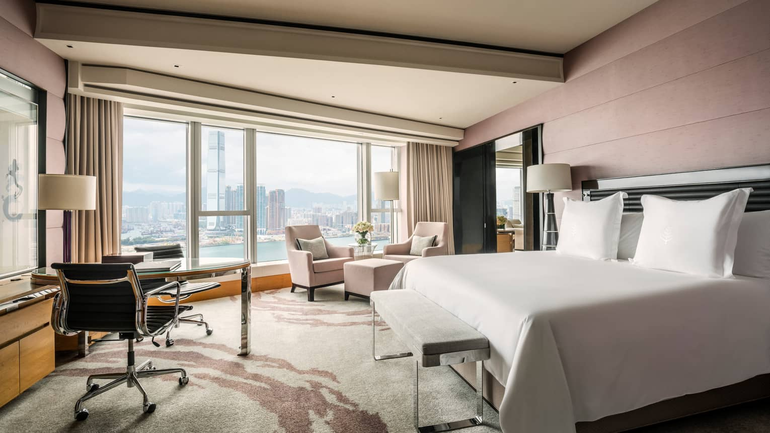 Hong Kong hotel room bed, desk, two armchairs and ottoman in front of floor-to-ceiling window, waterfront view