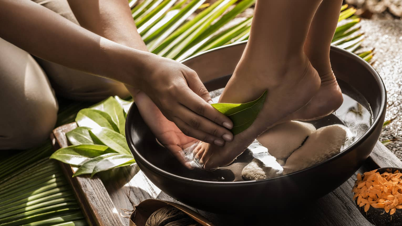 Close-up of woman's feet in round wood bowl as hands run tropical leaf over foot