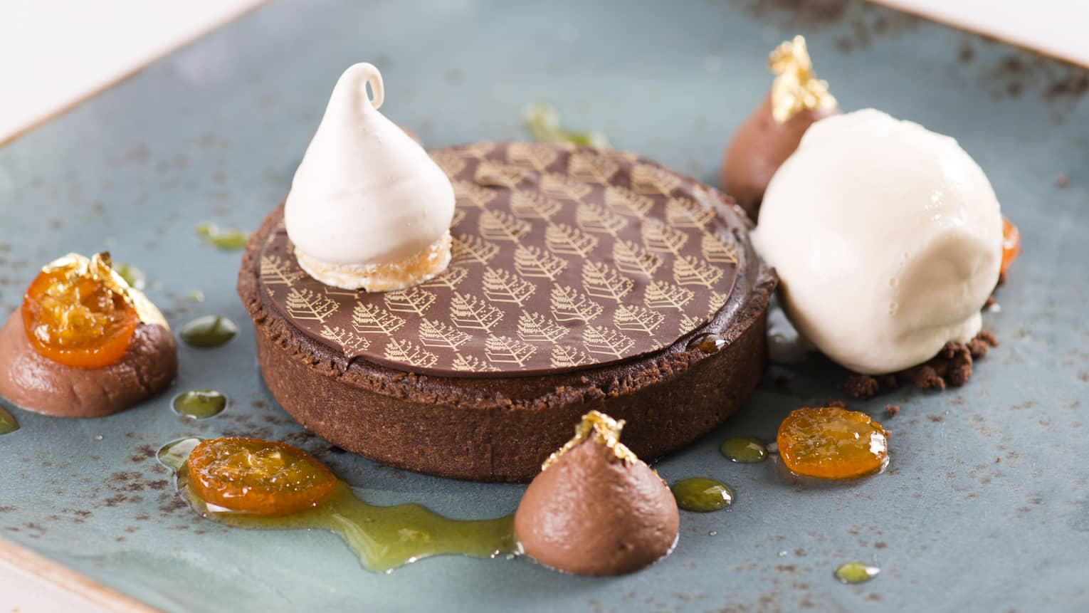 Tart covered by chocolate disc with Four Seasons logo print, small scoops of cream