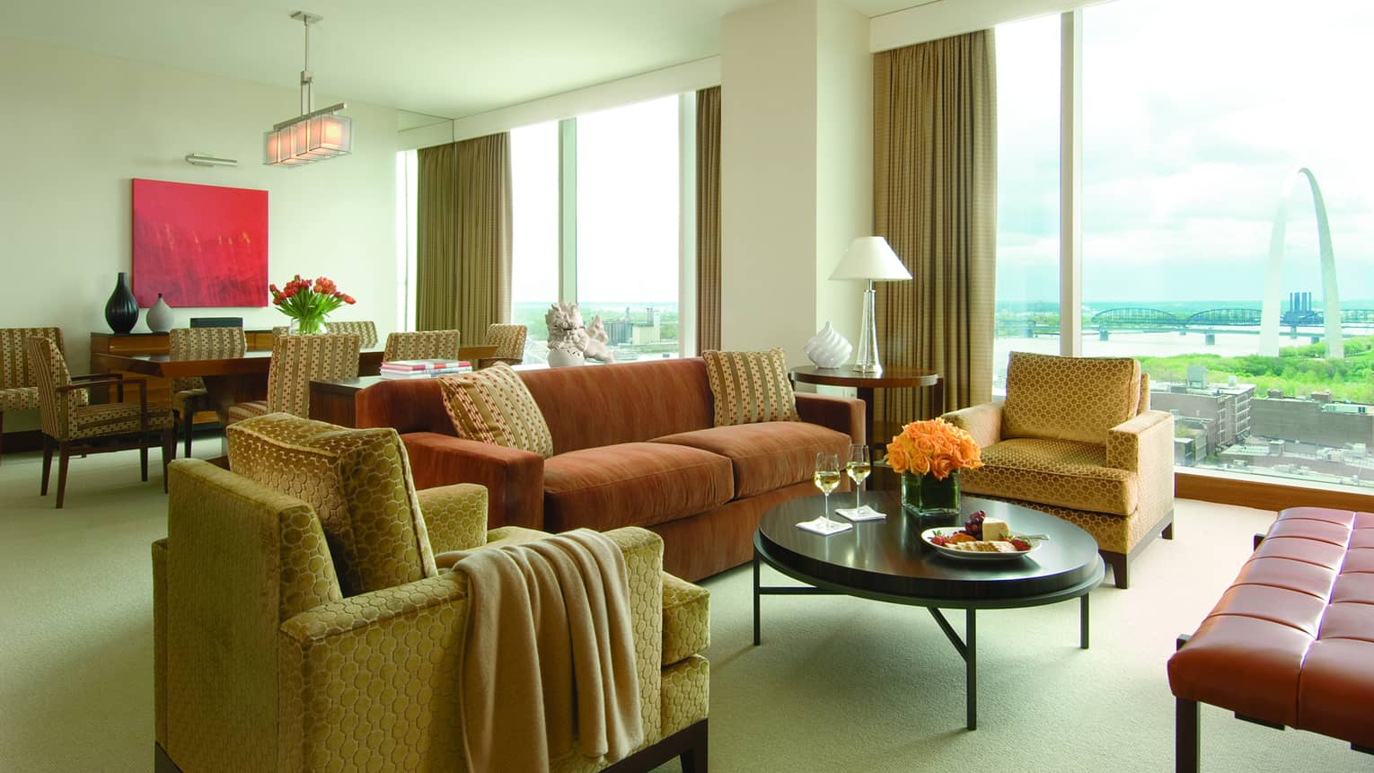 One-bedroom luxury suite living room with dark orange velvet sofa, gold velvet armchairs and leather bench