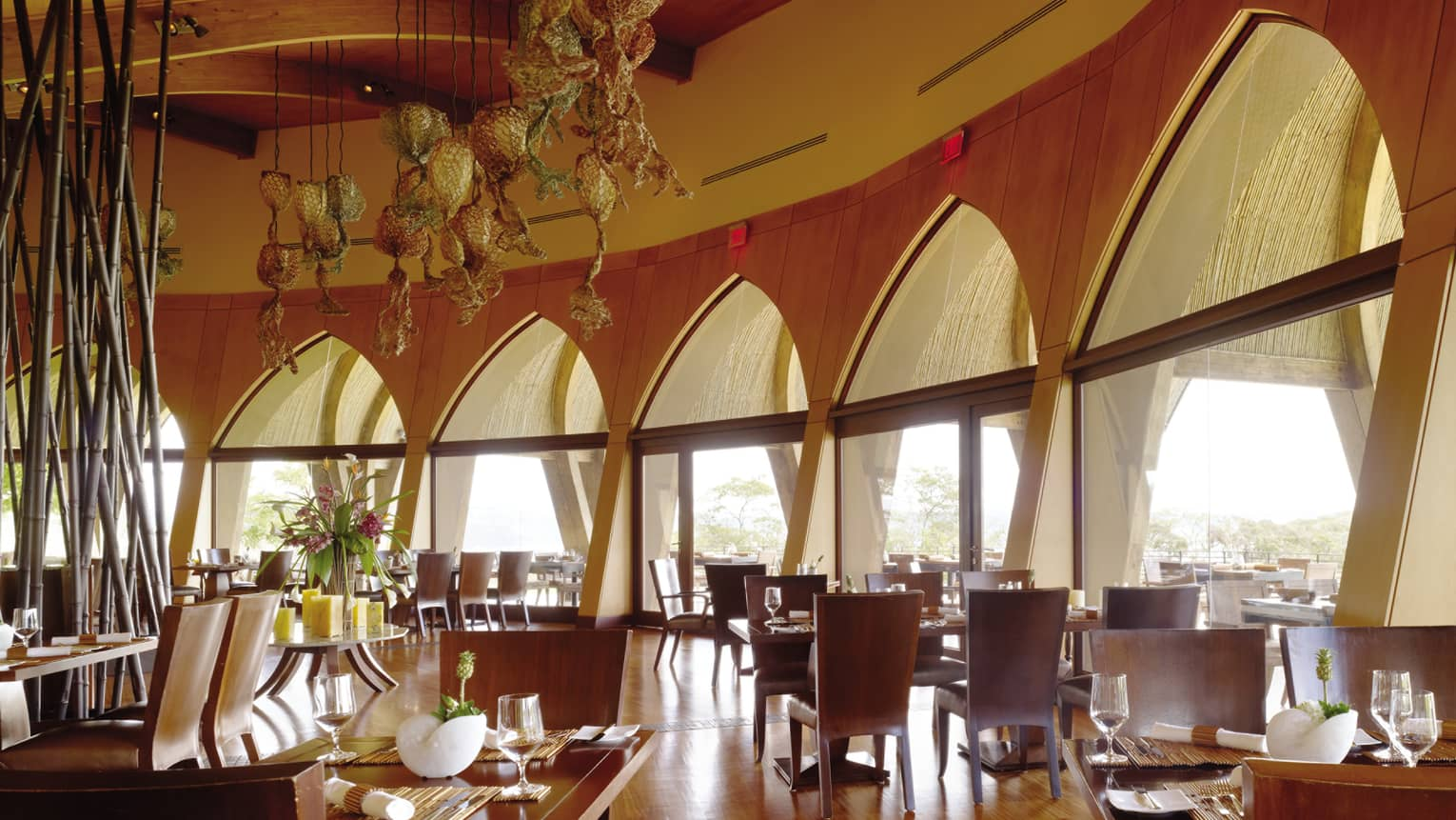 Caracol restaurant dining room with wood floors, curved wood walls lined with peak windows