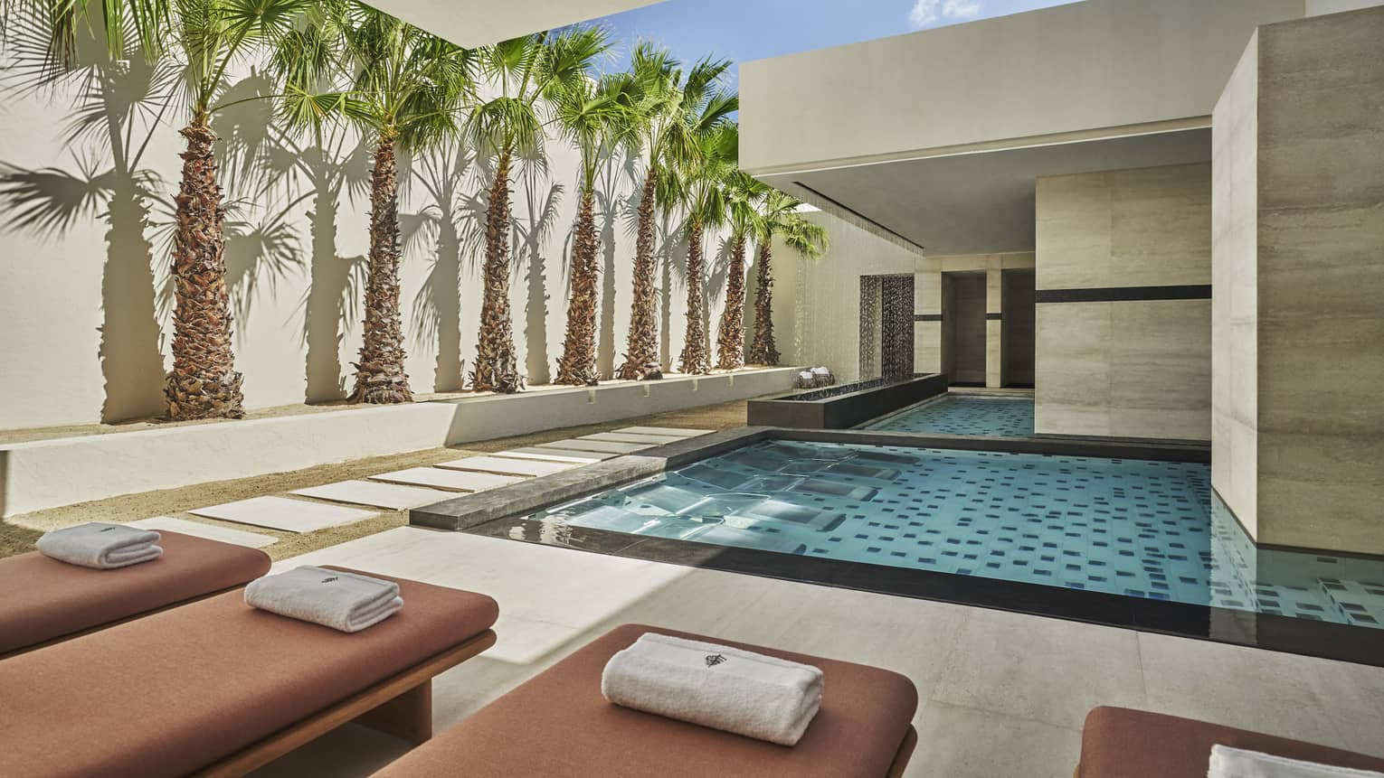 Lounge chairs line the four seasons resort los cabos indoor pool