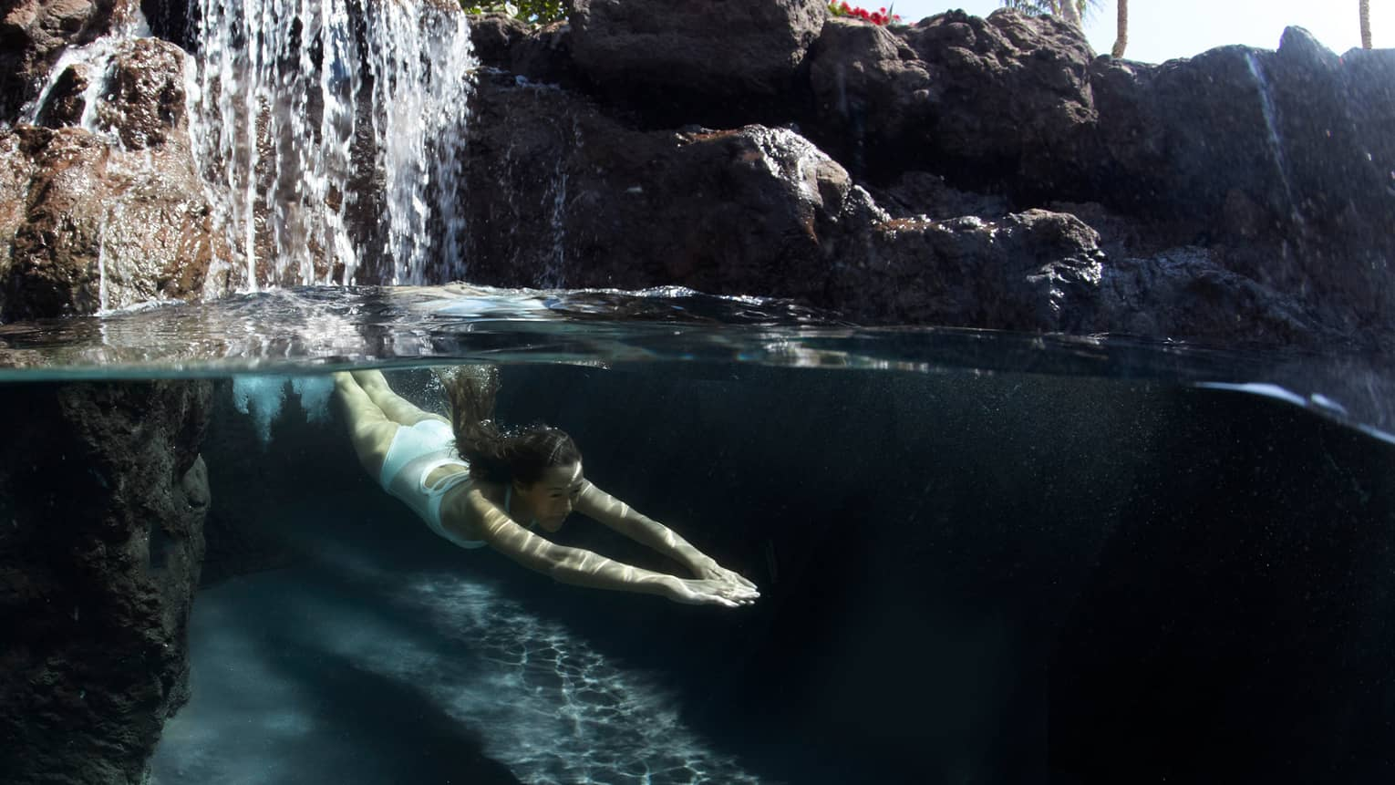 Woman dives underwater, waterfall behind her