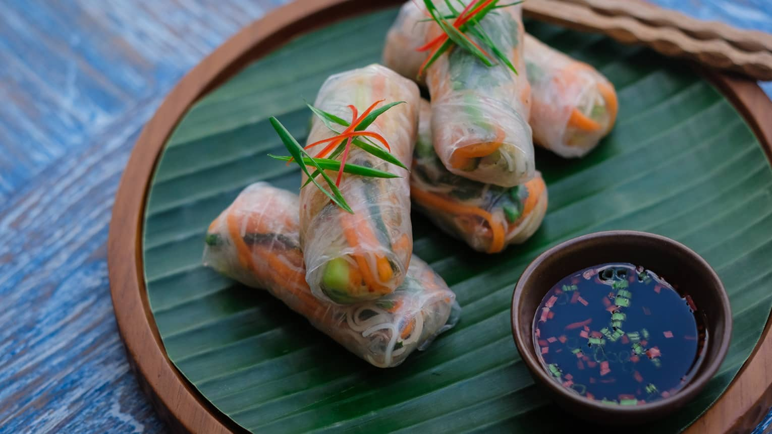 Fresh springrolls topped with a green herb on a wooden plate, along with a dish of fish sauce and wooden chopsticks