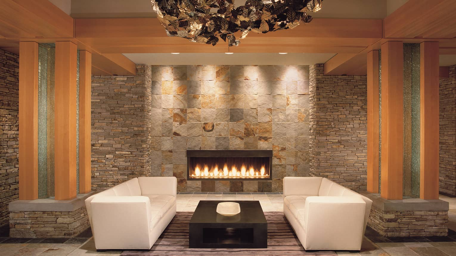 Two white sofas, coffee table by modern gas fireplace on stone wall under artistic chandelier