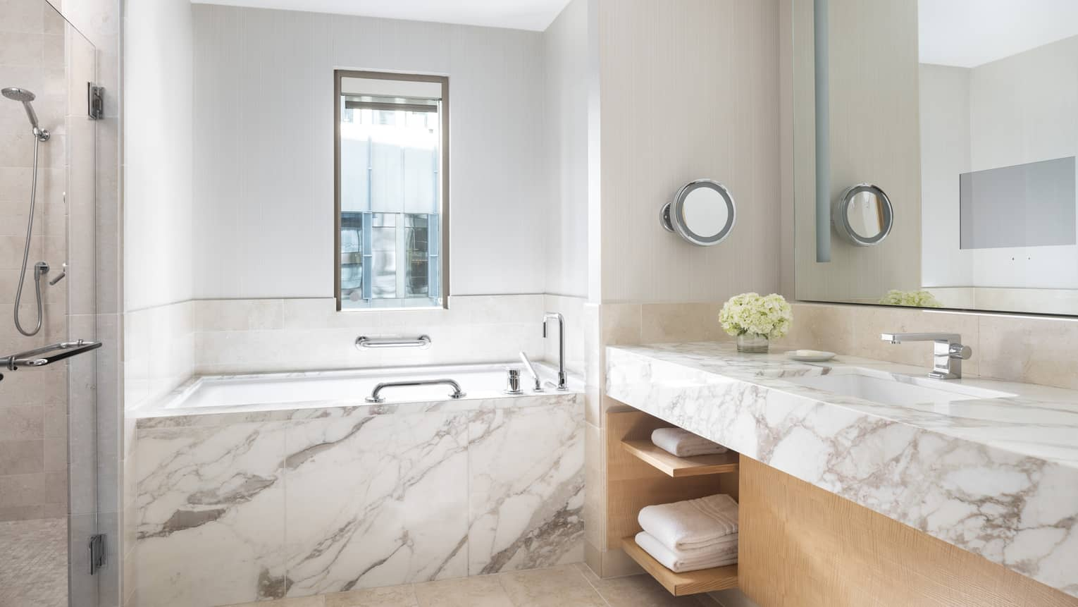 Marble counter and a marble bathtub gleam in a bathroom