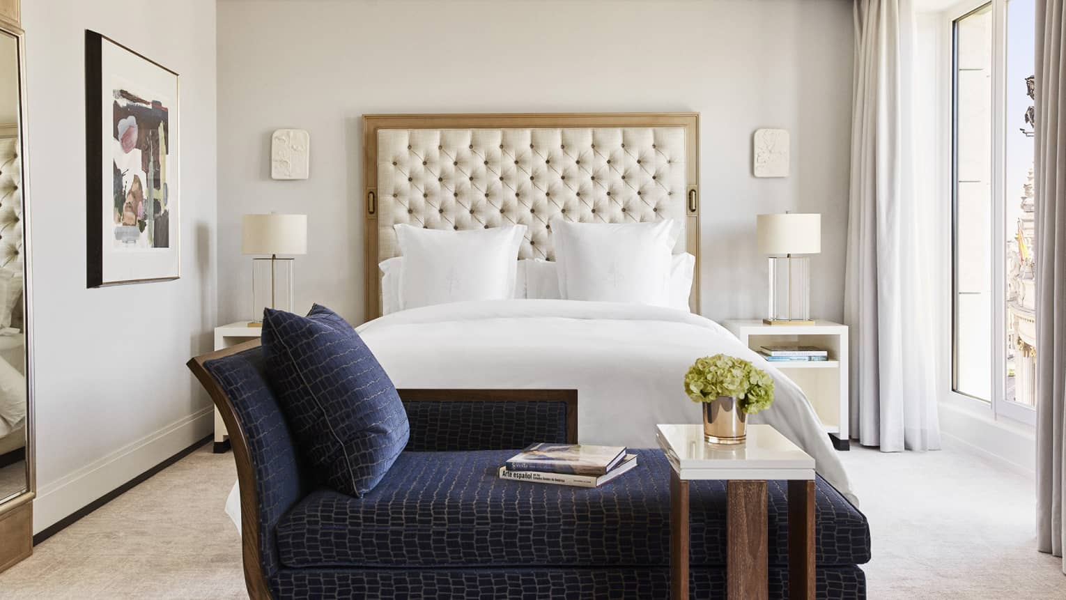Bedroom with king bed, tufted headboard, dark blue chaise lounge at foot of bed, white ceiling molding