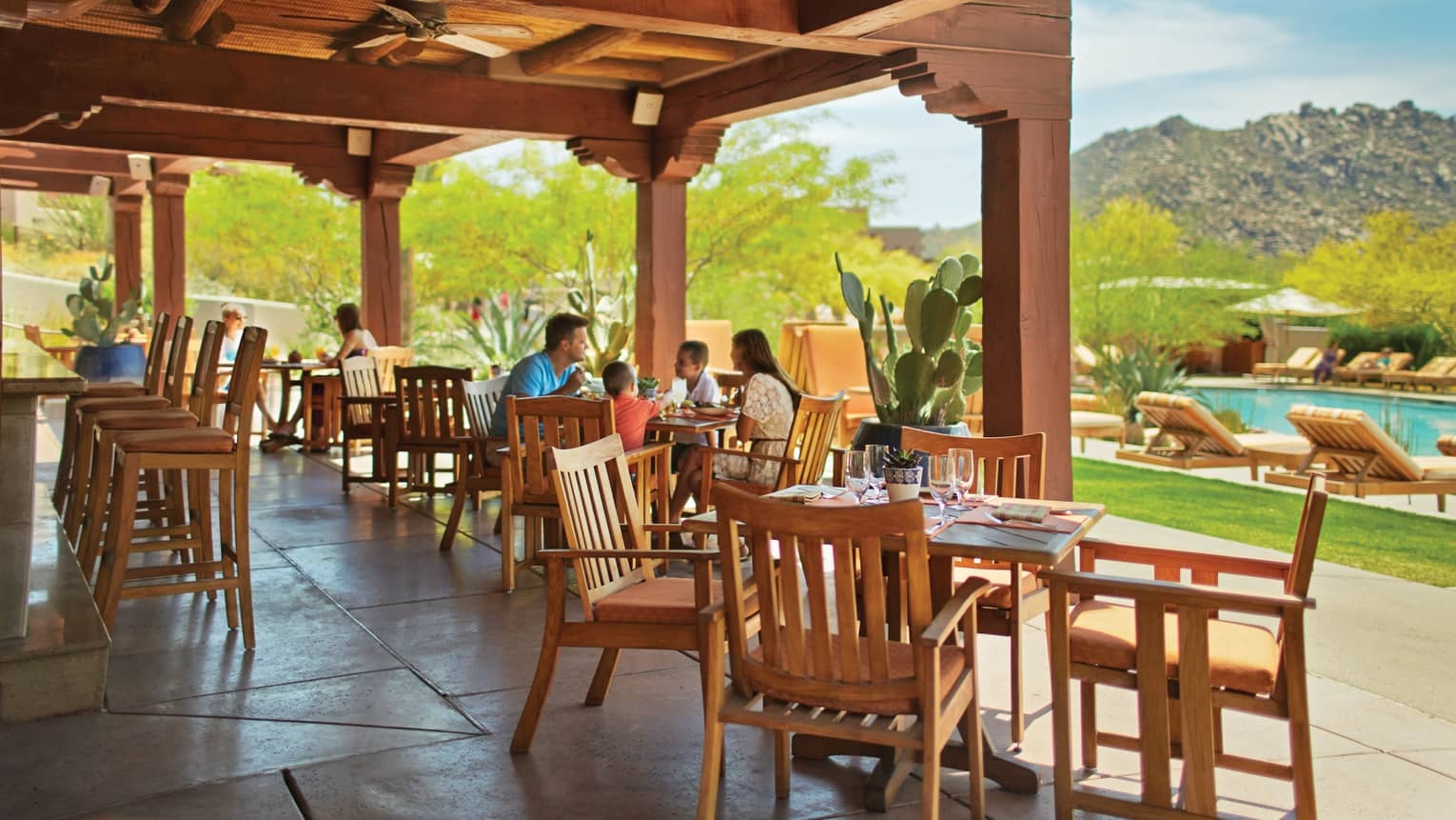 Families dining on Saguaro Blossom patio under wood pergola near swimming pool, deck on sunny day
