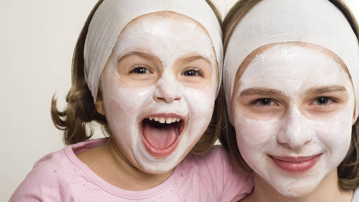 Two young girls with white clay spa masks on faces, towel wraps around foreheads