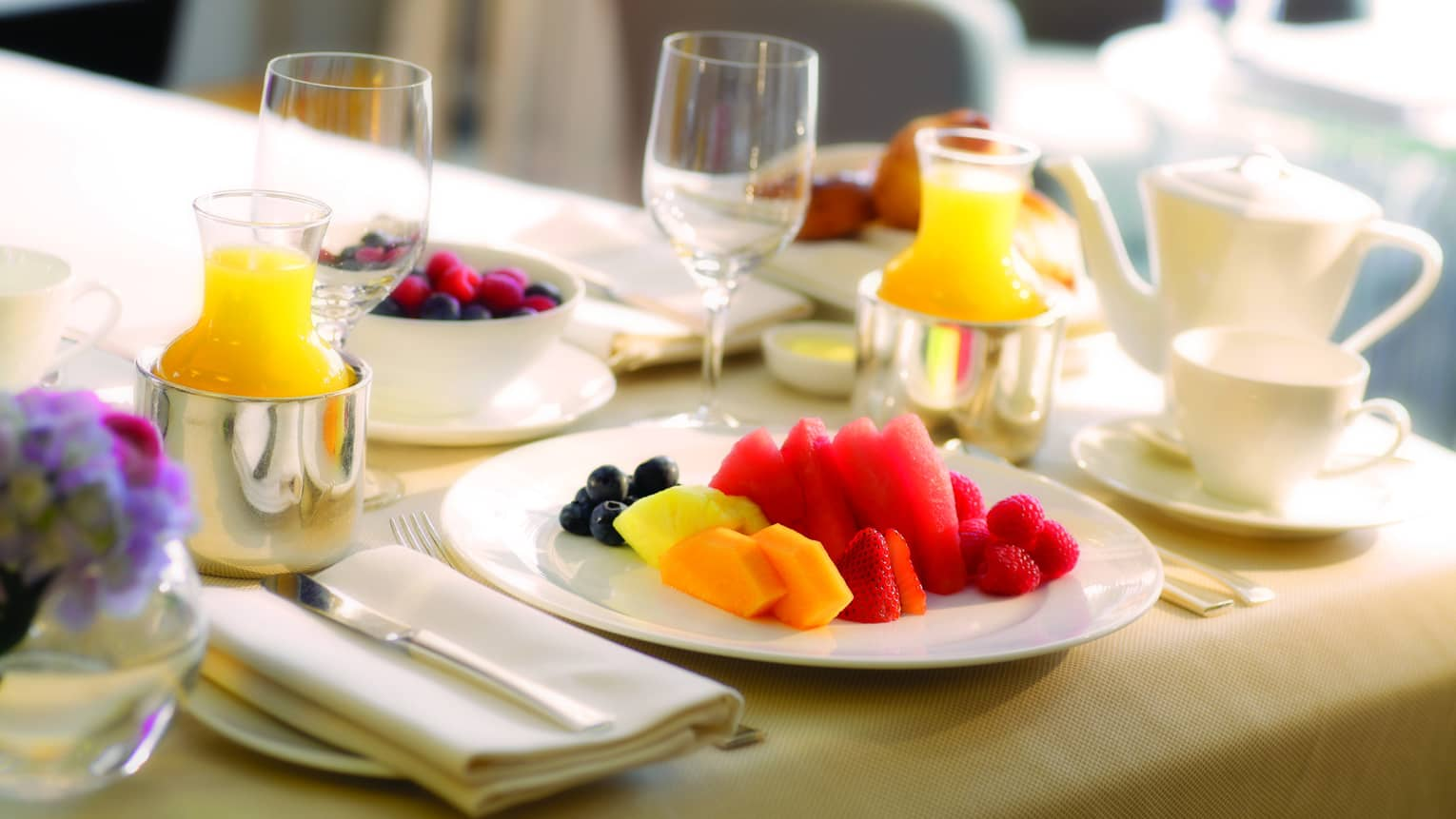 Close-up of in-room dining table service with plate of fresh melon and berries, tea and orange juice