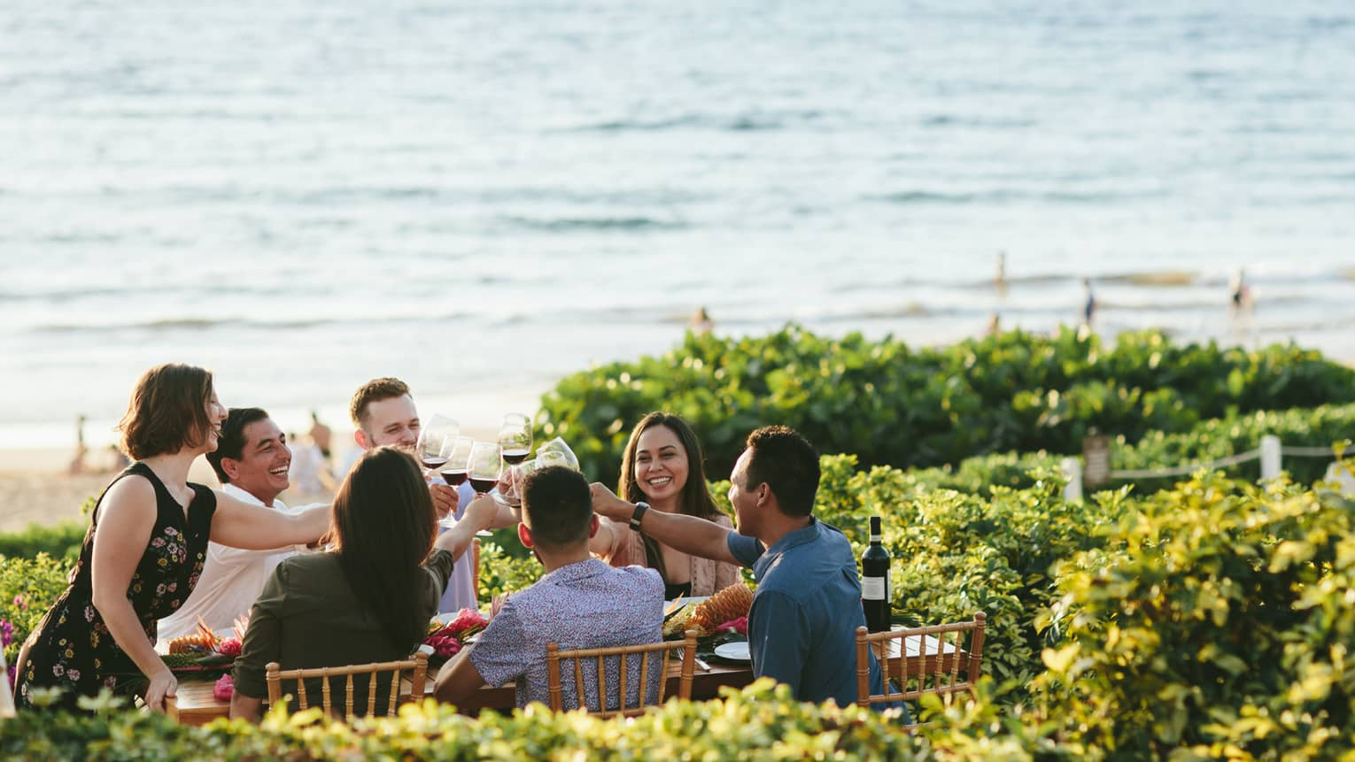 A group of guests make a toast at a beachfront dining location