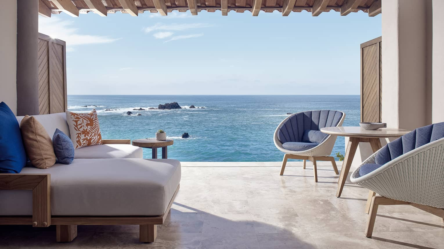 Sitting area with two chairs and one sofa, opening to the sea