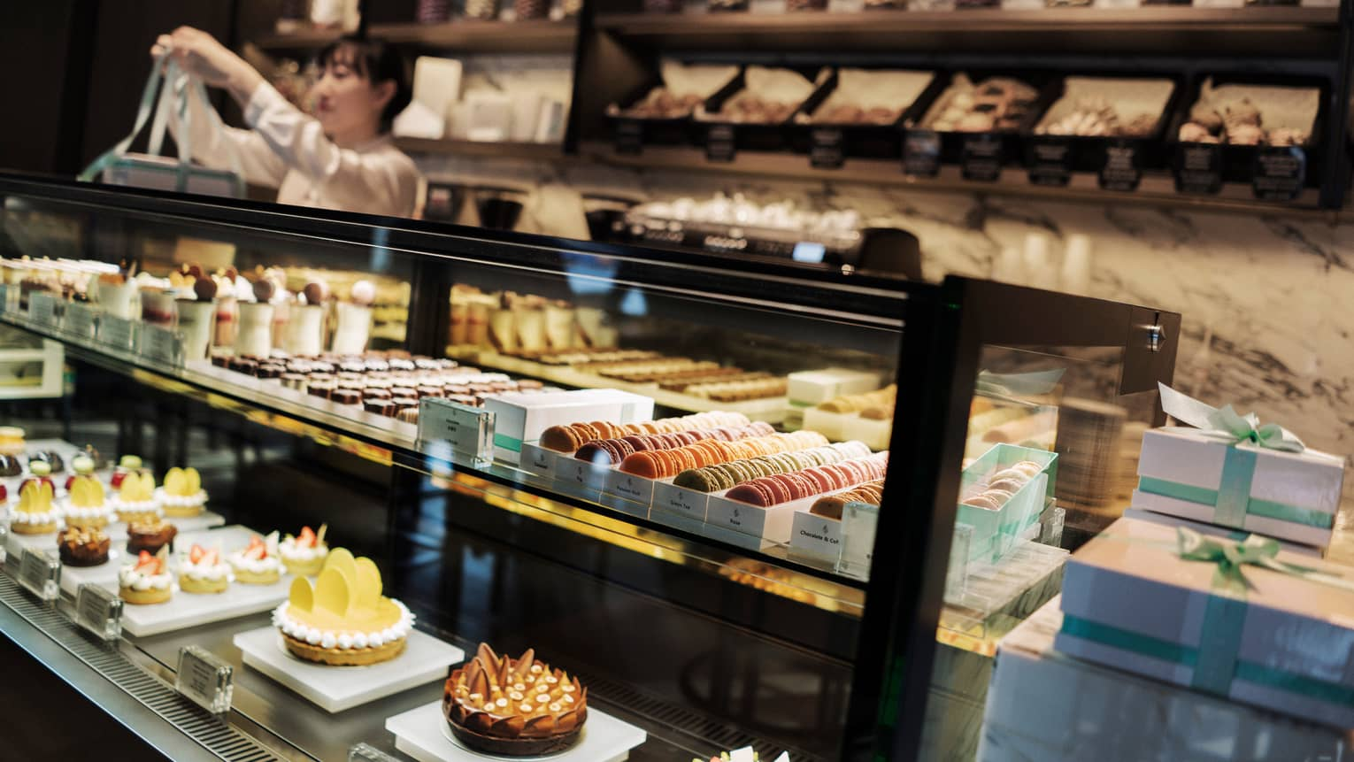 Pastry chef ties bow on box behind large glass counter with pastries, desserts