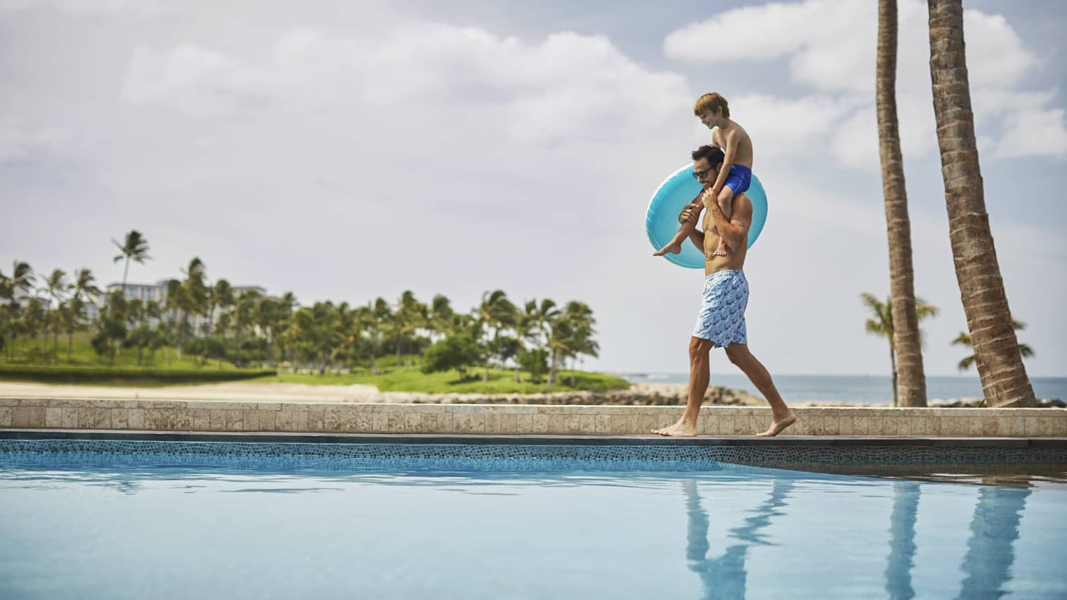 Man carries young boy on shoulders, blue inner tube as they walk by outdoor swimming pool