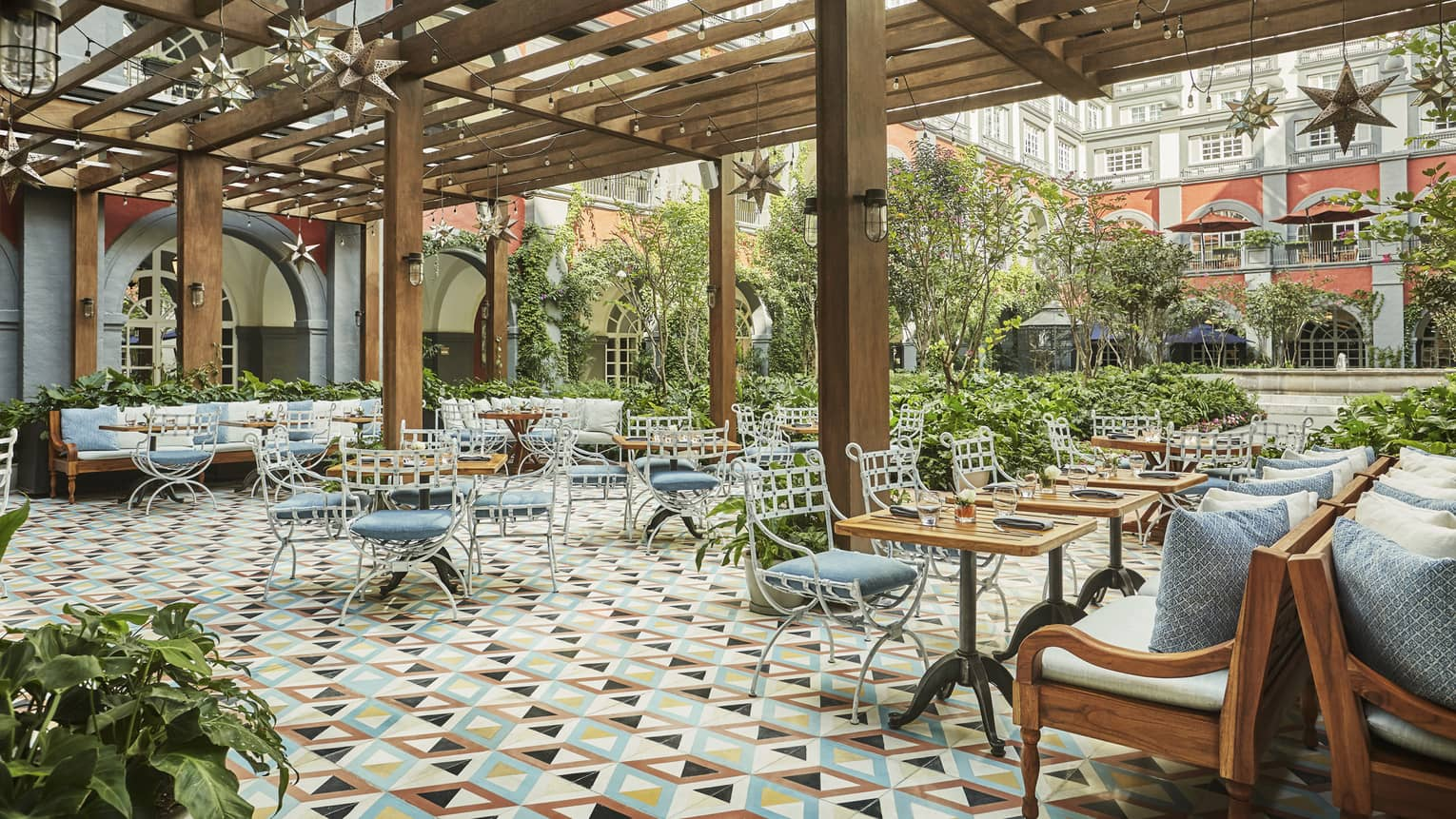 Colourful tiles,  iron patio chairs with blue cushions, tables under awning on Zanaya terrace