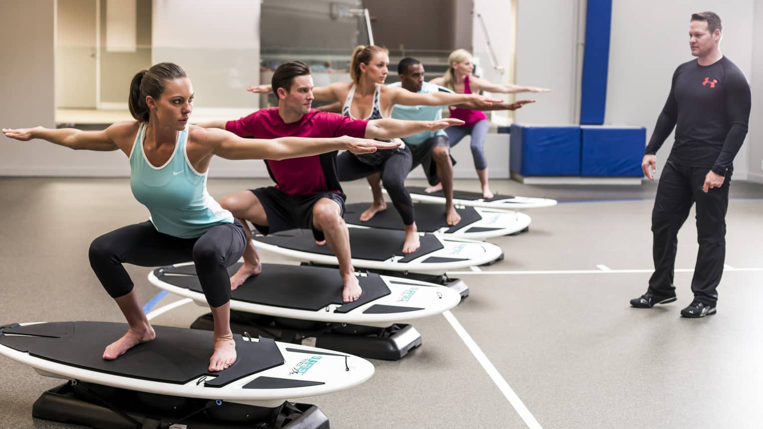 People extend arms, balance on small stationary surfboards in Fitness Centre