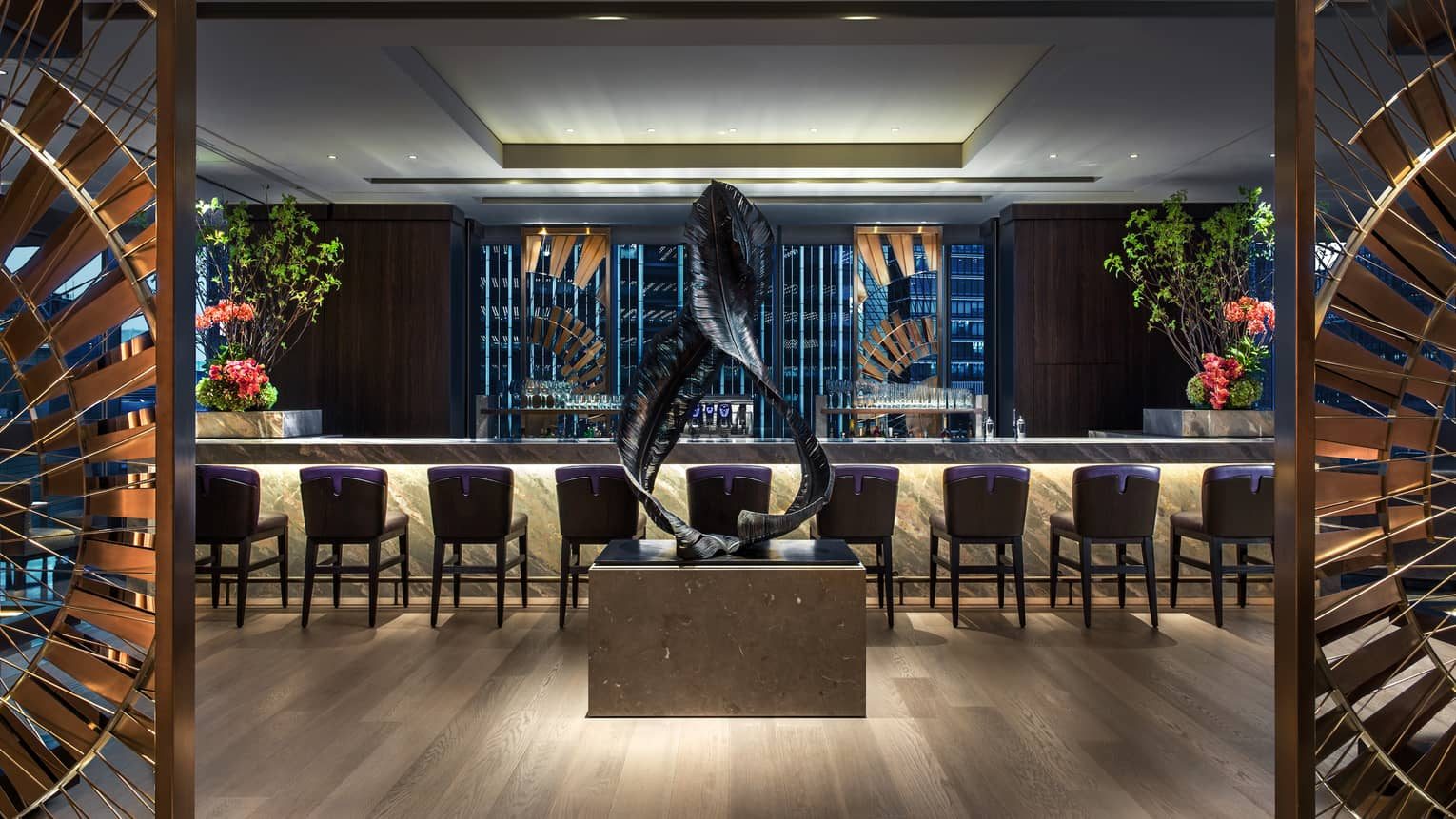 Large modern sculpture of two twisted black feathers in front of Motif bar, stools