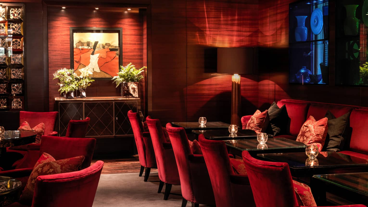 Red velvet chairs along Amaranto Lounge dining tables, modern wood walls, art, dim lighting