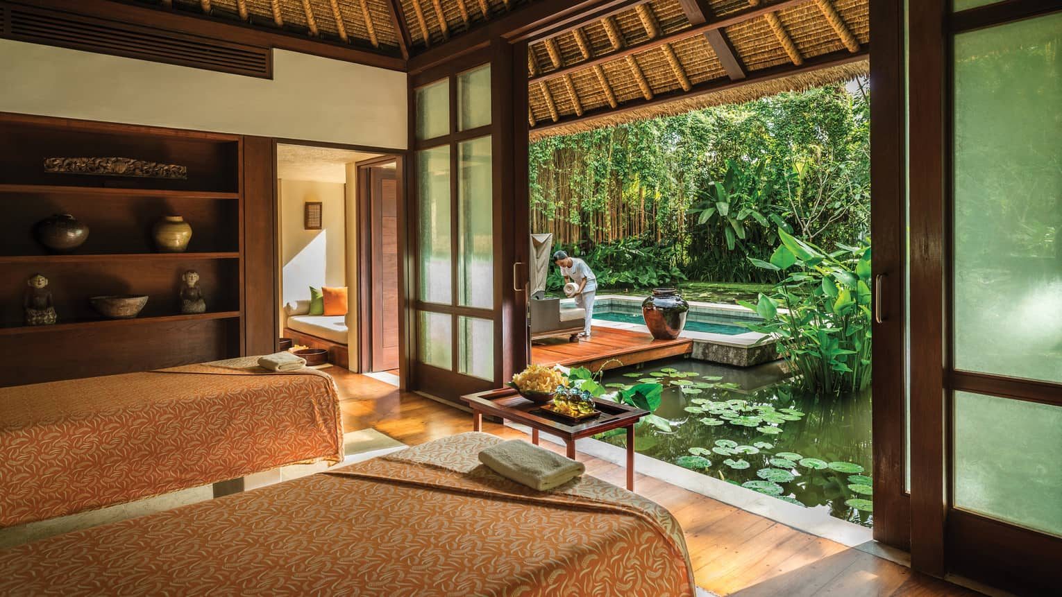 Two massage beds in spa room with door open to lily pond where spa attendant sets down rolled white towel
