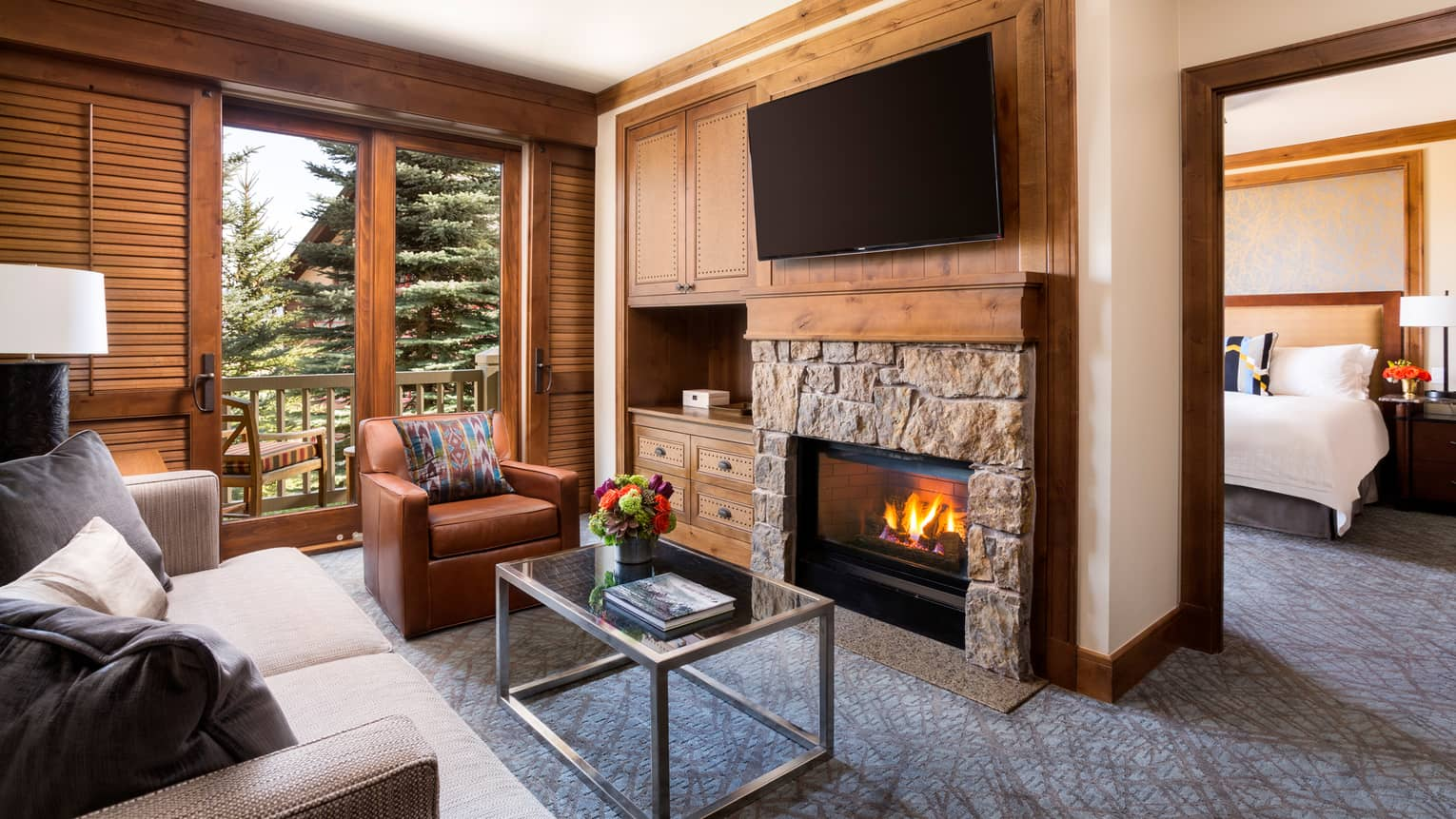 Stone gas fireplace under wood mantle, TV, leather armchair, glass coffee table