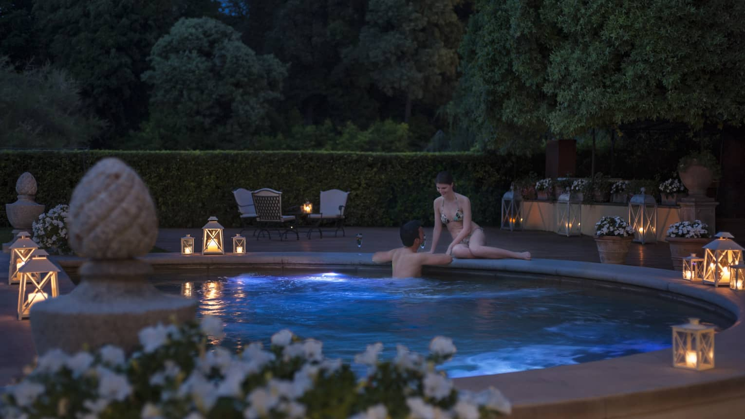 Woman sits on edge of outdoor whirlpool as man wades in water, glowing lanterns on deck