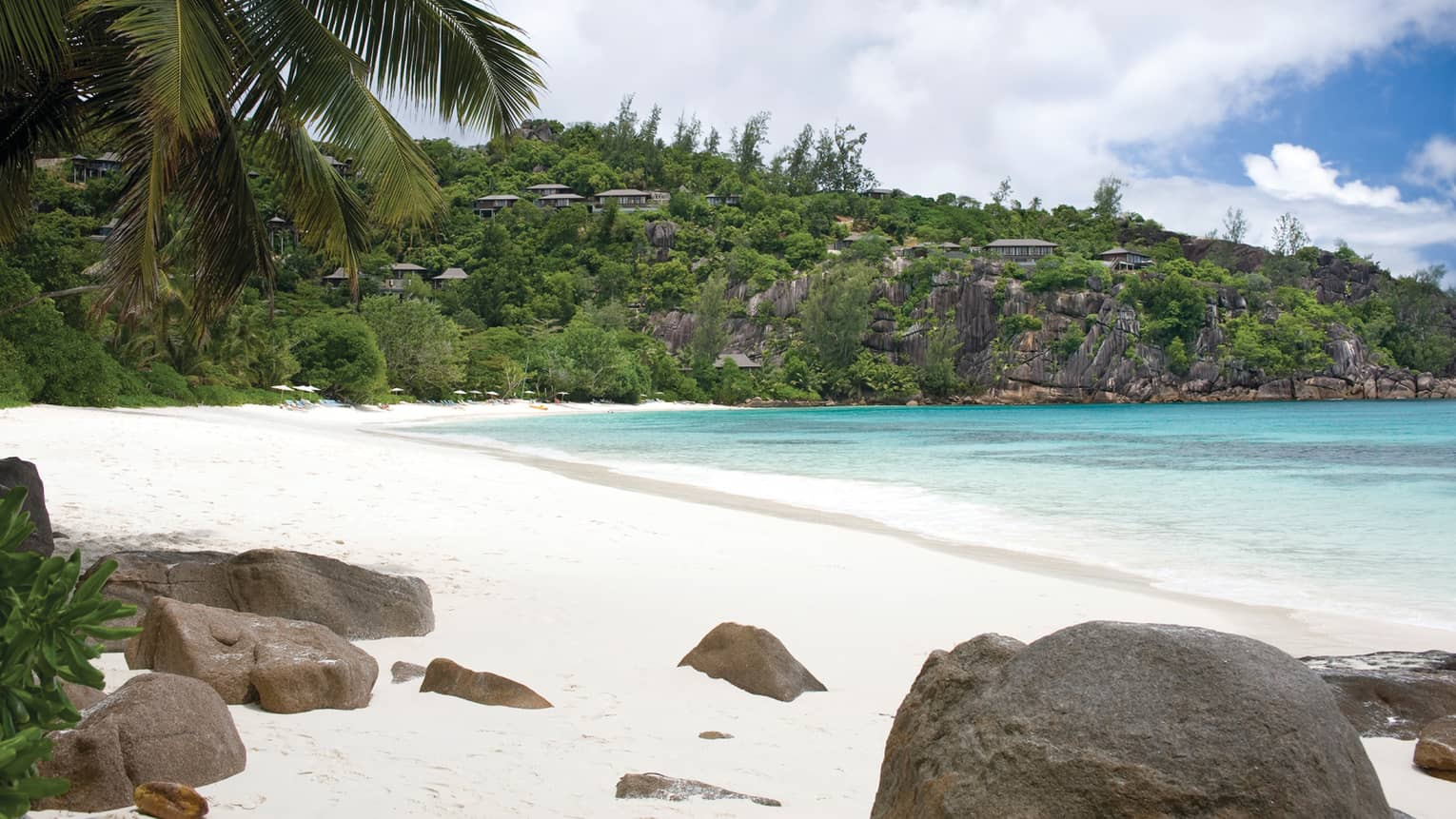 White sand beach with boulders, turquoise tide, palm trees on sunny day