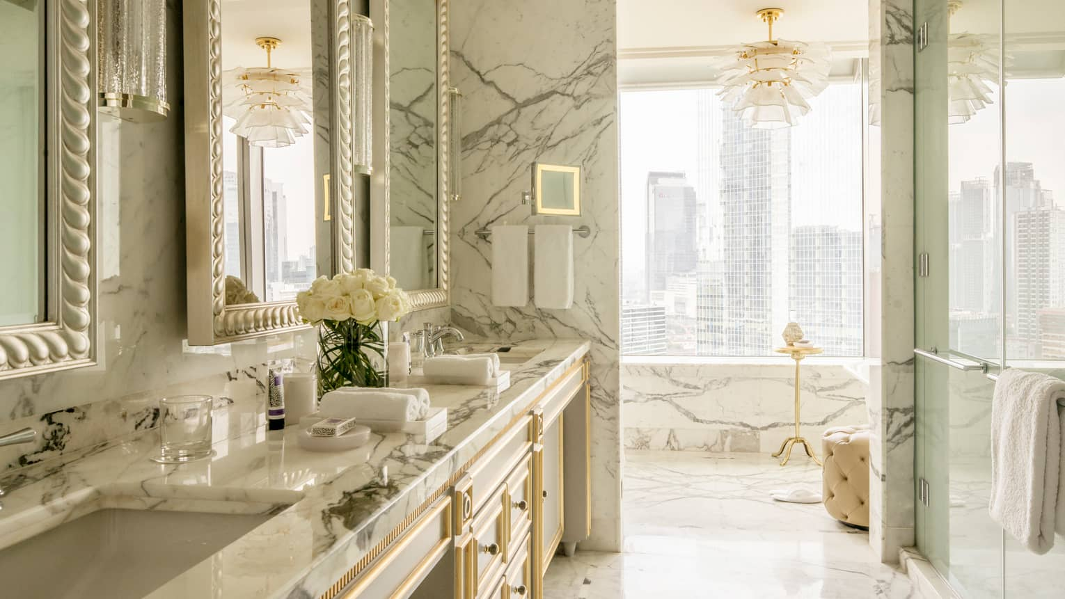 Presidential Suite bright white marble bathroom with double sink, glass shower, white chandelier, city views
