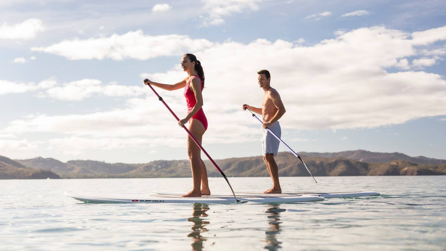 Man and woman wearing swimsuits hold paddles, balance on stand-up paddleboards on ocean